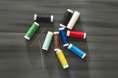Ράβοντας βελόνα και χρωματισμένα νήματα στροφίων, πολύχρωμα νήματα στροφίων, ράψιμο και ράβοντας βελόνες, ψαλίδι και ψαλίδι, που  Στοκ Εικόνες