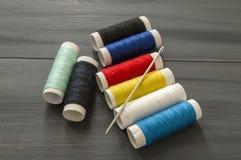 Ράβοντας βελόνα και χρωματισμένα νήματα στροφίων, πολύχρωμα νήματα στροφίων, ράψιμο και ράβοντας βελόνες, ψαλίδι και ψαλίδι, που  Στοκ εικόνα με δικαίωμα ελεύθερης χρήσης