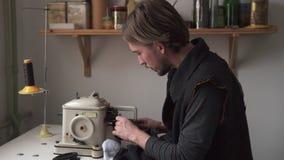 Ράβοντας γούνα ραφτών νεαρών άνδρων furrier στη μηχανή απόθεμα βίντεο