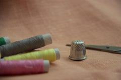 Ράβοντας εξάρτηση: πολύχρωμο νήμα, δακτυλήθρα, ψαλίδι σε ένα ύφασμα λινού Στοκ Εικόνα