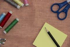 Ράβοντας εξάρτηση: πολύχρωμο νήμα, δακτυλήθρα, ψαλίδι σε ένα ύφασμα λινού Στοκ Εικόνες