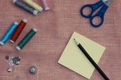 Ράβοντας εξάρτηση: πολύχρωμο νήμα, δακτυλήθρα, ψαλίδι σε ένα ύφασμα λινού Στοκ Φωτογραφία