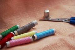 Ράβοντας εξάρτηση: πολύχρωμο νήμα, δακτυλήθρα, ψαλίδι σε ένα ύφασμα λινού Στοκ Φωτογραφίες