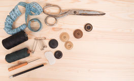 Ράβοντας εξαρτήματα σε ένα ξύλινο υπόβαθρο ανασκόπησης κουμπιών κινηματογραφήσεων σε πρώτο πλάνο ράβοντας νήμα δύο βελόνων έννοια Στοκ εικόνα με δικαίωμα ελεύθερης χρήσης
