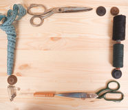 Ράβοντας εξαρτήματα σε ένα ξύλινο υπόβαθρο ανασκόπησης κουμπιών κινηματογραφήσεων σε πρώτο πλάνο ράβοντας νήμα δύο βελόνων έννοια Στοκ Φωτογραφίες