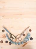 Ράβοντας εξαρτήματα σε ένα ξύλινο υπόβαθρο ανασκόπησης κουμπιών κινηματογραφήσεων σε πρώτο πλάνο ράβοντας νήμα δύο βελόνων έννοια Στοκ φωτογραφία με δικαίωμα ελεύθερης χρήσης