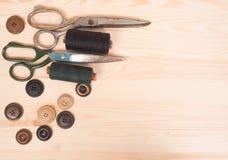 Ράβοντας εξαρτήματα σε ένα ξύλινο υπόβαθρο ανασκόπησης κουμπιών κινηματογραφήσεων σε πρώτο πλάνο ράβοντας νήμα δύο βελόνων έννοια Στοκ Εικόνα