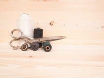 Ράβοντας εξαρτήματα σε ένα ξύλινο υπόβαθρο ανασκόπησης κουμπιών κινηματογραφήσεων σε πρώτο πλάνο ράβοντας νήμα δύο βελόνων έννοια Στοκ φωτογραφίες με δικαίωμα ελεύθερης χρήσης