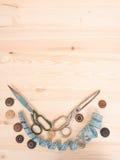 Ράβοντας εξαρτήματα σε ένα ξύλινο υπόβαθρο ανασκόπησης κουμπιών κινηματογραφήσεων σε πρώτο πλάνο ράβοντας νήμα δύο βελόνων έννοια Στοκ εικόνες με δικαίωμα ελεύθερης χρήσης
