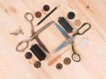 Ράβοντας εξαρτήματα σε ένα ξύλινο υπόβαθρο ανασκόπησης κουμπιών κινηματογραφήσεων σε πρώτο πλάνο ράβοντας νήμα δύο βελόνων έννοια Στοκ Εικόνες