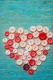 Ράβοντας κουμπιά με μορφή μιας καρδιάς Στοκ Εικόνες