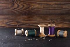Ράβοντας νήμα στις σπείρες, ύφασμα, βελόνες για το ράψιμο στο ξύλινο υπόβαθρο Σύνολο για την προσαρμογή των προϊόντων, το πλέξιμο Στοκ Εικόνες