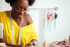 Ράβοντας ύφασμα με τη βελόνα seamstress στον εργασιακό χώρο στοκ εικόνα