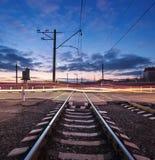 Ράγα που διασχίζει με τα θολωμένα φω'τα αυτοκινήτων στο όμορφο ηλιοβασίλεμα Railw Στοκ εικόνες με δικαίωμα ελεύθερης χρήσης