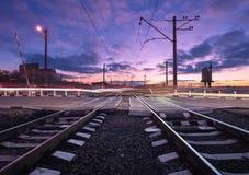 Ράγα που διασχίζει με τα θολωμένα φω'τα αυτοκινήτων στο όμορφο ηλιοβασίλεμα Railw Στοκ φωτογραφίες με δικαίωμα ελεύθερης χρήσης
