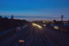 Ράγες και διάβαση του τραίνου τη νύχτα Στοκ Φωτογραφίες