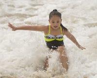 Ράντισμα κοριτσιών Amerasian στα ωκεάνια κύματα Στοκ Εικόνα