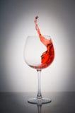 Ράντισμα κόκκινου κρασιού γυαλιού σε ένα άσπρο υπόβαθρο Στοκ Εικόνες