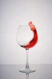 Ράντισμα κόκκινου κρασιού γυαλιού σε ένα άσπρο υπόβαθρο Στοκ εικόνα με δικαίωμα ελεύθερης χρήσης