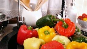 Ράντισμα νερού βρύσης από τα πιπέρια κουδουνιών στο νεροχύτη κουζινών απόθεμα βίντεο