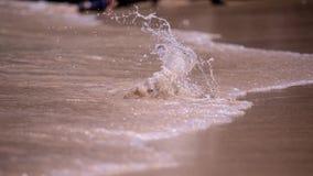 Ράντισμα νερού πέρα από μια μικρή πέτρα σε μια παραλία άμμου στοκ εικόνες
