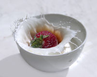 Ράντισμα φραουλών στο φλυτζάνι του γάλακτος Στοκ εικόνα με δικαίωμα ελεύθερης χρήσης