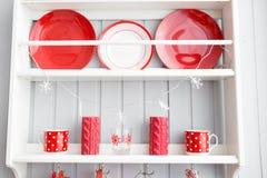 Ράφια με τα πιάτα Εσωτερική ανοικτό γκρι κουζίνα και κόκκινο ντεκόρ Χριστουγέννων Προετοιμάζοντας το μεσημεριανό γεύμα στο σπίτι  στοκ εικόνα με δικαίωμα ελεύθερης χρήσης