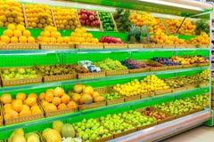 Ράφι με τα φρέσκα οργανικά φρούτα σε μια υπεραγορά αγροτικής αγοράς Apple, πορτοκάλι, σταφύλια, persimmon, ακτινίδιο, ανανάς, αχλ Στοκ Φωτογραφία