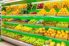 Ράφι με τα φρέσκα οργανικά φρούτα σε μια υπεραγορά αγροτικής αγοράς Apple, πορτοκάλι, σταφύλια, persimmon, ακτινίδιο, ανανάς, αχλ Στοκ εικόνες με δικαίωμα ελεύθερης χρήσης