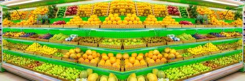Ράφι με τα φρέσκα οργανικά φρούτα σε μια υπεραγορά αγροτικής αγοράς Apple, πορτοκάλι, σταφύλια, persimmon, ακτινίδιο, ανανάς, αχλ Στοκ Εικόνες