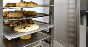 Ράφι με τις unbaked ζύμες στο εργαστήριο αρτοποιείων στοκ εικόνες