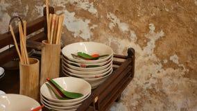 Ράφι με το ασιατικό dishware Ξύλινο ράφι με τη διάφορη ασιατική ένωση dishware κοντά στο θρυμματιμένος τοίχο στην κουζίνα απόθεμα βίντεο