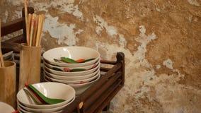 Ράφι με το ασιατικό dishware Ξύλινο ράφι με τη διάφορη ασιατική ένωση dishware κοντά στο θρυμματιμένος τοίχο στην κουζίνα φιλμ μικρού μήκους