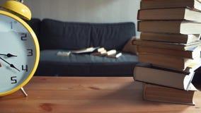 Ράφι με το μεγάλους κίτρινους ρολόι και το σωρό των βιβλίων Μετακινηθείτε τον πυροβολισμό απόθεμα βίντεο