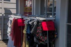 Ράφι των ενδυμάτων των γυναικών με τα κόκκινα σημάδια πώλησης εκρήξεων έξω σε ένα πεζοδρόμιο μπροστά από ένα κατάστημα ιματισμού στοκ εικόνες με δικαίωμα ελεύθερης χρήσης