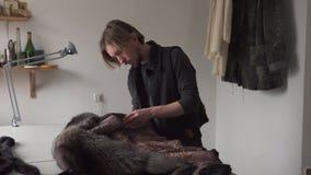 Ράφτης ατόμων σχετικά με τη γούνα για το ράψιμο του παλτού furrier στο εργαστήριο φιλμ μικρού μήκους
