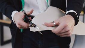 Ράφτης και σχεδιαστής μόδας με το τέμνον ύφασμα ψαλιδιού στο στούντιο ατελιέ Κινηματογράφηση σε πρώτο πλάνο: το ψαλίδι κόβει τον  φιλμ μικρού μήκους