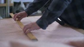 Ράφτης που χαρακτηρίζει το ύφασμα με την κιμωλία για την κοπή φιλμ μικρού μήκους