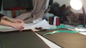 ράφτης Ύφασμα ψαλιδιού ραφτών ` s ραφτών εγκοπών χεριών Θηλυκό ράβοντας υλικό ραφτών στον εργασιακό χώρο Προετοιμασία του υφάσματ απόθεμα βίντεο