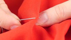Ράψιμο γυναικών με τη βελόνα και τη δακτυλήθρα στο κόκκινο ύφασμα απόθεμα βίντεο