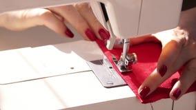 Ράψιμο γυναικών με τη σύγχρονη ράβοντας μηχανή Ένα χέρι που υποστηρίζει ένα ύφασμα δεράτων ράβοντας σε μια μηχανή Κόκκινο ύφασμα  απόθεμα βίντεο