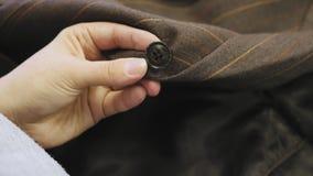 Ράψιμο ενός κουμπιού επάνω σε ένα καφετί προσαρμοσμένο σακάκι κοστούμι φιλμ μικρού μήκους
