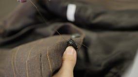 Ράψιμο ενός κουμπιού επάνω σε ένα καφετί προσαρμοσμένο σακάκι κοστούμι απόθεμα βίντεο