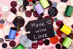 Ράψιμο - που γίνεται με τον πίνακα αγάπης με τα κουμπιά και το νήμα Στοκ Φωτογραφία
