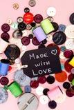 Ράψιμο - που γίνεται με τον πίνακα αγάπης με τα κουμπιά και το νήμα Στοκ Εικόνες