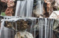 Ρέοντας κίνηση καταρρακτών στην πέτρα στον κήπο Στοκ Εικόνα