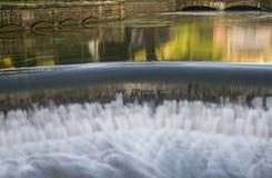 ρέοντας νερό πέρα από το μικρό προκαλούμενο από τον άνθρωπο καταρράκτη Στοκ φωτογραφίες με δικαίωμα ελεύθερης χρήσης