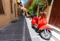 Ρέτχυμνο, νησί Κρήτη, Ελλάδα, - 1 Ιουλίου 2016: Ένα κόκκινο παλαιό σταθμευμένο μηχανικό δίκυκλο και ένας τοπικός πολίτης στο τέλο στοκ εικόνες