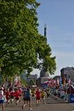 Ρήγα, Λετονία - 19 Μαΐου 2019: Οι δρομείς μαραθωνίου που φθάνουν στο άγαλμα ελευθερίας με τις παραδοσιακά ντυμένες μαζορέτες δίνο στοκ φωτογραφίες