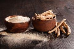 Ρίζα και σκόνη Ashwagandha στα ξύλινα φλυτζάνια στο σκοτεινό υπόβαθρο στοκ εικόνες